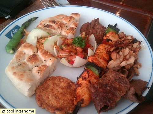 A mix of different breads and kebabs and salads